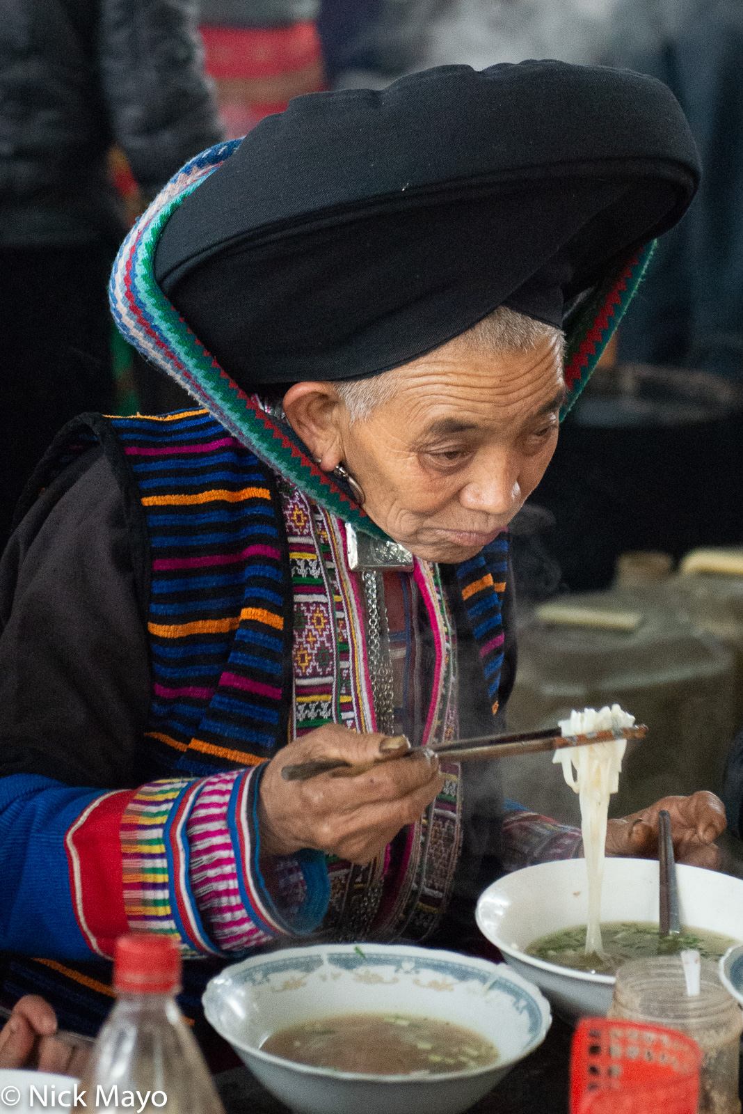 A Dao Ta Pan woman eating noodles at Lung Phin market.