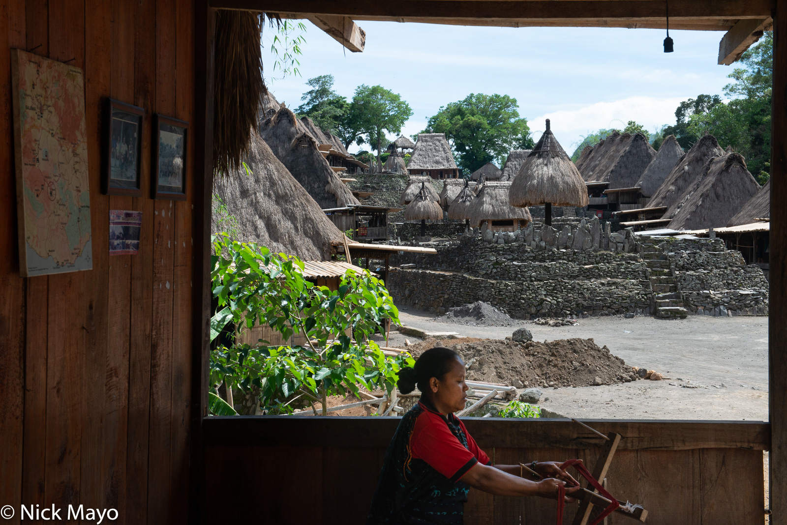 A woman spinning thread on a wooden spindle in the thatched roof Ngada Regency village of Bena with its bhaga and ngadhu ceremonial...