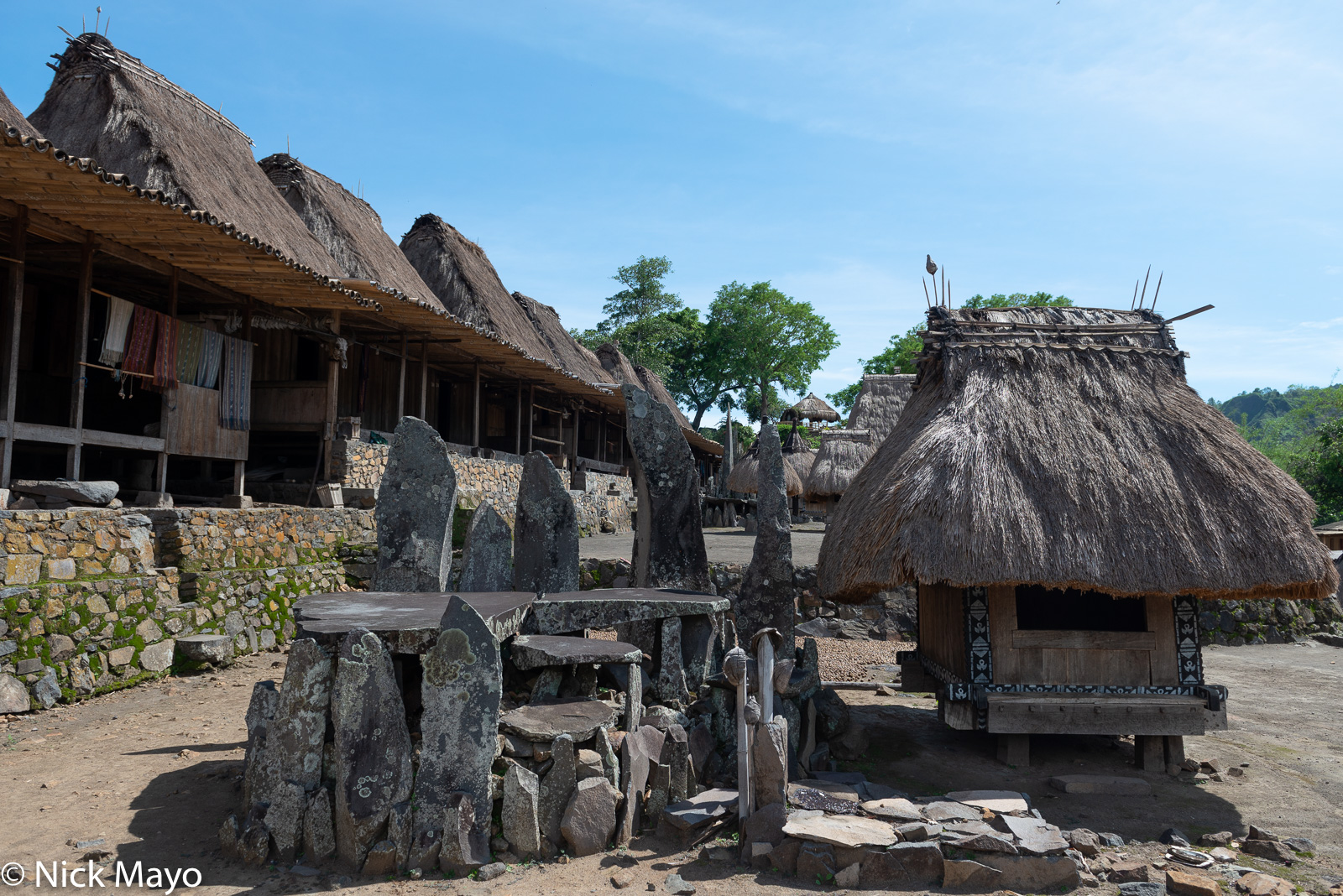 A watu lewa (stone altar) and thatched roofed bhaga in the Ngada Regency village of Bena.