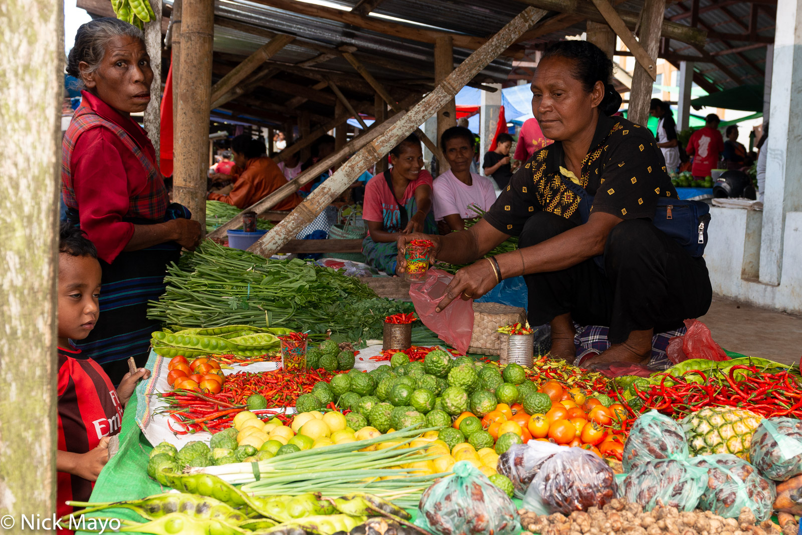 A vendor selling fruit and vegetables at Mataloko market in Ngada Regency.