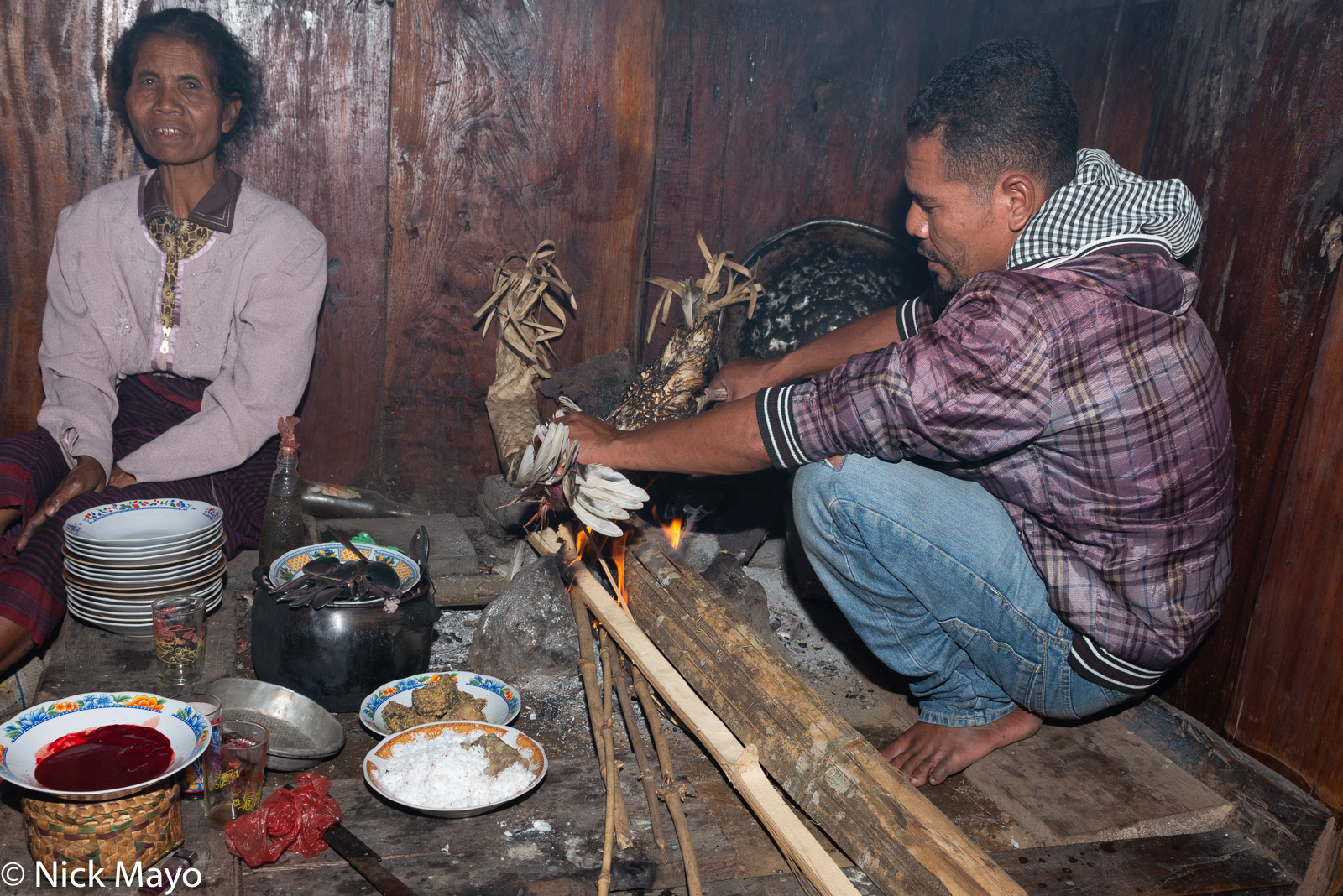 Ritual roasting of a chicken at the conclusion of the reba ceremony in a Ngada Regency village.