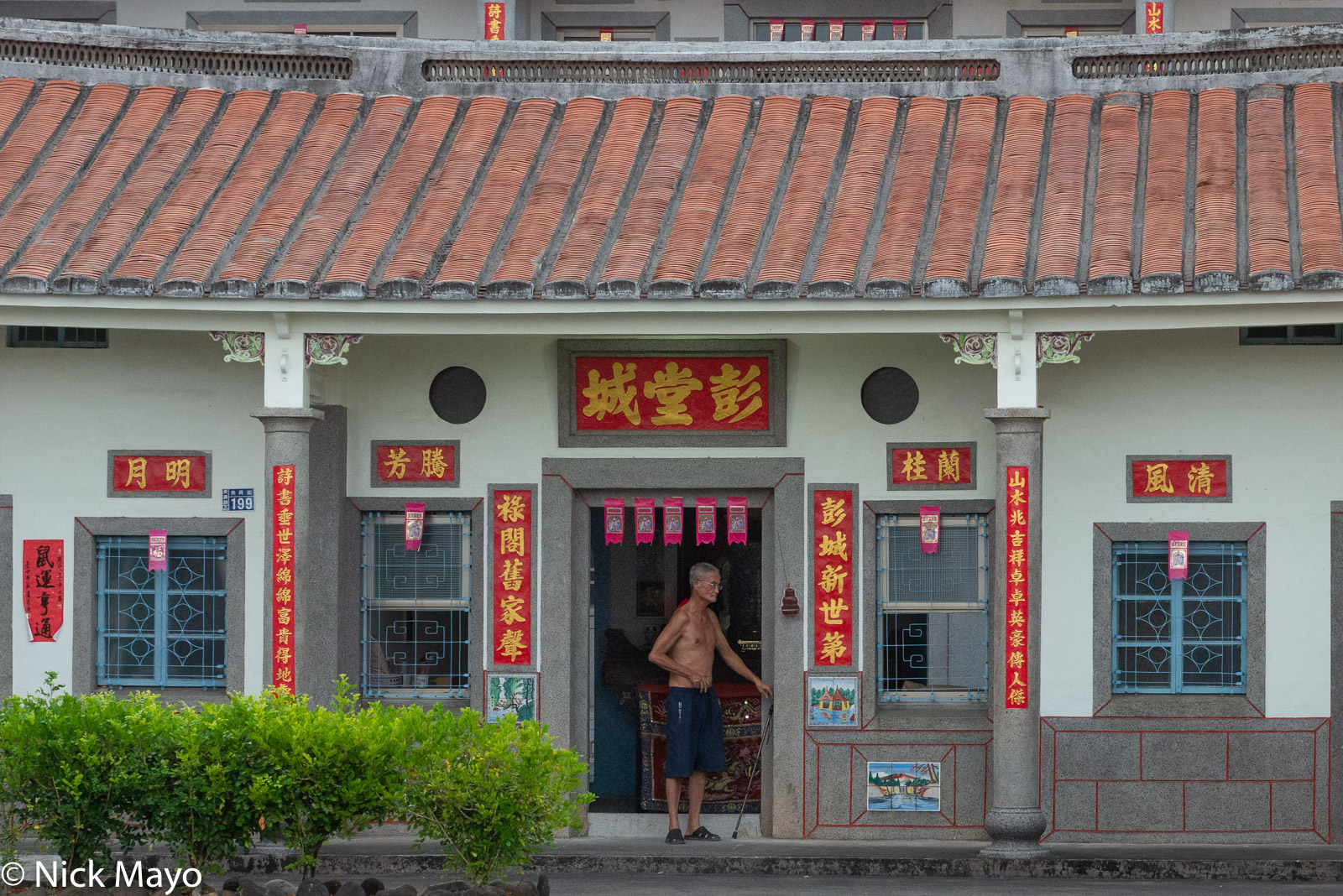A man standing in the doorway of his residence in Meinong district.
