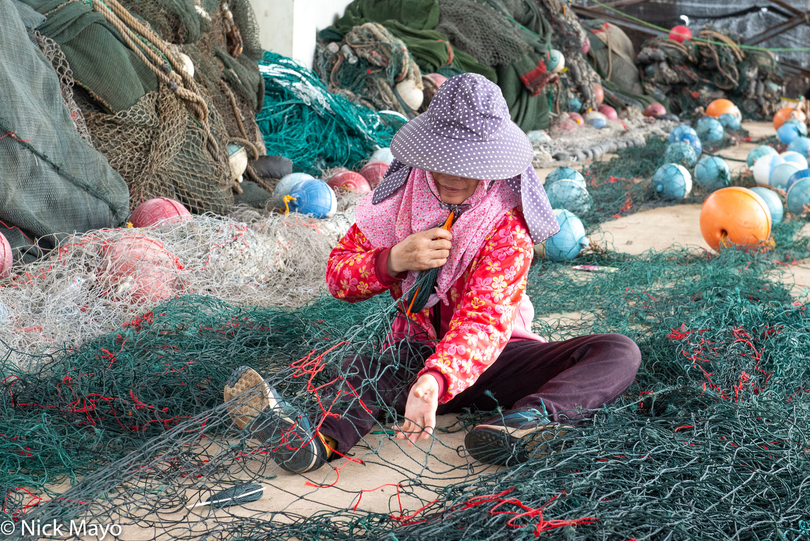 Repairing fishing nets at Wai'an port.