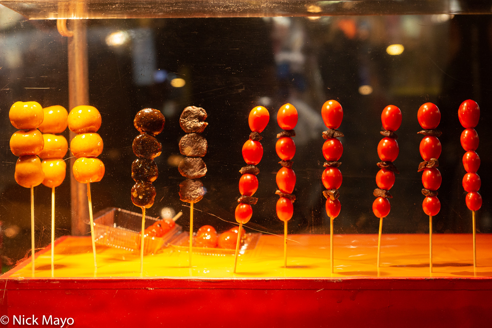 Snacks on sale in a scratched perspex box at a night market stand in Taipei's Wanhua district.